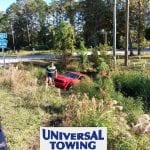 universal towing Daytona provides towing services for red Dodge Challenger in retention pond