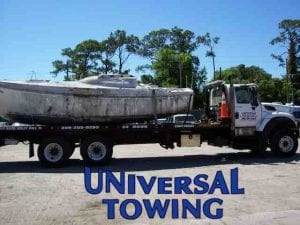 Boat that needs a tow in transit to the dump